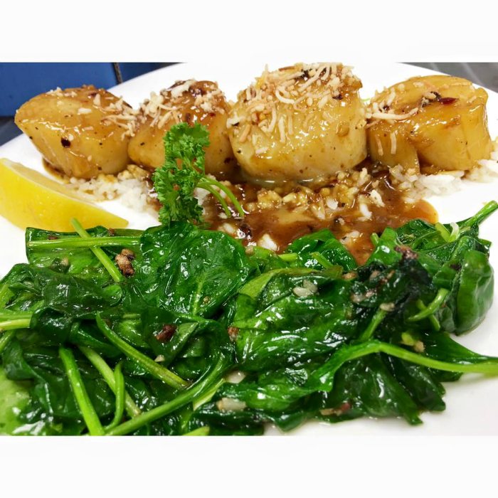 FRESH SEA SCALLOPS PREPARED KOKOMO STYLE, SERVED WITH SATUÉED SPINACH